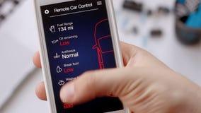 El hombre comprueba la información del coche sobre su dispositivo móvil Mala condición, reparación de la necesidad del coche Coch metrajes