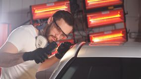 El hombre comprueba el resultado del pulido del coche con una linterna almacen de video