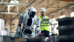 El hombre comprueba el robot que se mueve mientras que mecanografía en una tableta en una fábrica almacen de metraje de vídeo