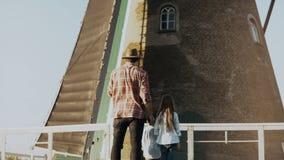 El hombre con dos niños hace una pausa el molino de viento holandés viejo El solo padre con la hija y el hijo miran un molino eno almacen de video