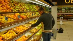 El hombre con el carro de la compra elige naranjas en el hipermercado fotos de archivo libres de regalías