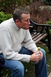 El hombre con el cigarrillo y vacia la botella de la bebida Fotografía de archivo
