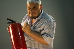 El hombre con el extintor rojo Imagen de archivo libre de regalías
