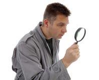 El hombre con el impermeable está mirando con la lupa sobre los vagos blancos imágenes de archivo libres de regalías