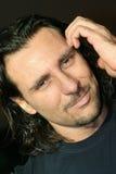El hombre con el pelo largo rasguña su cabeza Foto de archivo