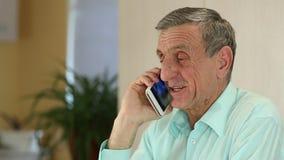 El hombre con el smartphone blanco habla y sonríe almacen de metraje de vídeo