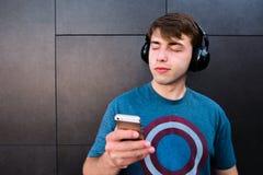 El hombre con el suyo observa cerrado, y el teléfono en sus manos, disfruta de música en auriculares inalámbricos en el fondo de  Fotos de archivo libres de regalías