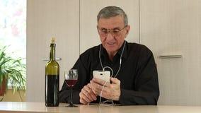 El hombre con el teléfono celular se sienta en la tabla y bebe el vino almacen de metraje de vídeo