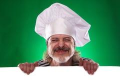 El hombre con la barba gris en un cocinero del traje y del sombrero de marinero que la cartelera aisló Foto de archivo