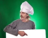 El hombre con la barba gris en un cocinero del traje y del sombrero de marinero que la cartelera aisló Imagen de archivo