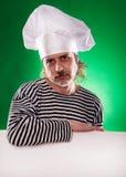 El hombre con la barba gris en un cocinero del traje y del sombrero de marinero que la cartelera aisló Fotos de archivo