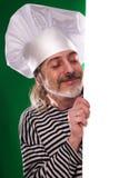 El hombre con la barba gris en un cocinero del traje y del sombrero de marinero que la cartelera aisló Imagenes de archivo