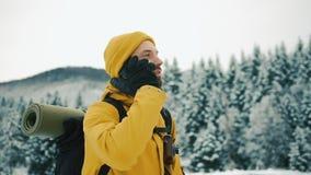 El hombre con la barba, invierno amarillo que lleva viste hablar en el teléfono Un caminante entra en las montañas del invierno c metrajes