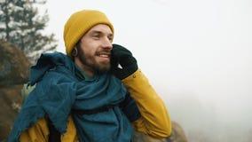 El hombre con la barba, invierno amarillo que lleva viste hablar en el teléfono Un caminante entra en las montañas del invierno c almacen de video