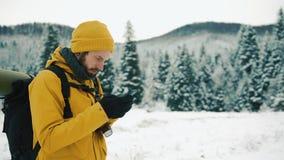 El hombre con la barba, invierno amarillo que lleva viste usando un teléfono Un caminante entra en las montañas del invierno con  metrajes