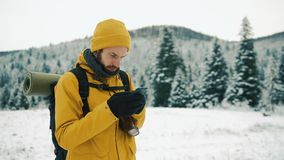 El hombre con la barba, invierno amarillo que lleva viste usando un teléfono Un caminante entra en las montañas del invierno con  almacen de metraje de vídeo