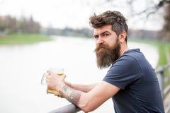 El hombre con la barba larga parece relajado Hombre con la barba y bigote en la cara tranquila, fondo del río, defocused Hombre b imágenes de archivo libres de regalías