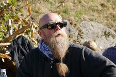 El hombre con la barba larga sonríe, y disfruta de los rayos de la sol pasados en el otoño, festival de la cosecha fotografía de archivo libre de regalías