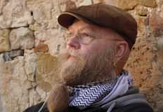 El hombre con la barba larga, vidrios y casquillo, se sienta cuidadosamente por una pared fotografía de archivo libre de regalías