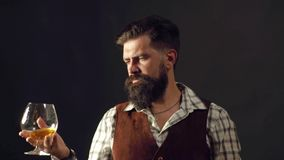 El hombre con la barba sostiene el brandy de cristal El camarero del hombre con la barba sostiene el brandy de cristal Concepto d almacen de video