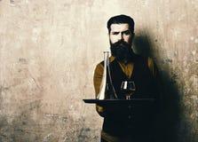 El hombre con la barba sostiene el coñac en el fondo beige, espacio de la copia Servicio y concepto de las bebidas del restaurant imágenes de archivo libres de regalías