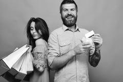 El hombre con la barba sostiene la tarjeta de crédito y la caja de dinero Fotos de archivo libres de regalías