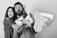 El hombre con la barba sostiene la tarjeta y la hucha de crédito El par celebra los panieres y el abrazo en fondo rosado Imagen de archivo libre de regalías