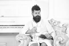 El hombre con la barba y el bigote disfruta de mañana mientras que se sienta en la butaca de lujo Hombre soñoliento en la alborno foto de archivo