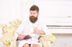 El hombre con la barba y el bigote disfruta de mañana mientras que se sienta en la butaca de lujo Hombre soñoliento en la alborno fotos de archivo