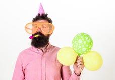 El hombre con la barba y el bigote en cara tranquila sostiene los balones de aire, fondo blanco Inconformista en gafas de sol gig fotos de archivo libres de regalías
