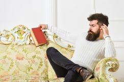 El hombre con la barba y el bigote pasa ocio con el libro Científico, profesor en cara estricta que analiza la literatura self fotos de archivo