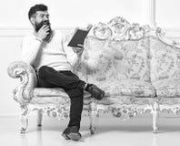 El hombre con la barba y el bigote se sienta en el sofá barroco del estilo, controles reserva, el fondo blanco de la pared Indivi fotos de archivo libres de regalías