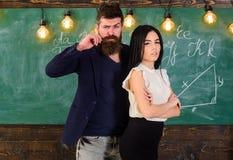 El hombre con la barba y el profesor atractivo de la muchacha se colocan en la sala de clase, pizarra en fondo Profesor y mirada  Imagen de archivo libre de regalías