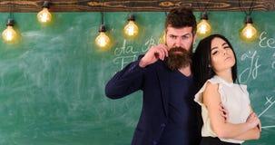 El hombre con la barba y el profesor atractivo de la muchacha se colocan en la sala de clase, pizarra en fondo Partners concepto  Foto de archivo libre de regalías