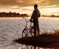 El hombre con la bici en las manos del río Salida del sol Fotografía de archivo libre de regalías