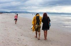 El hombre con la bufanda y los dreadlocks grandes y la mujer en vestido y pelo rojo largo caminan a lo largo de la playa en Byron foto de archivo