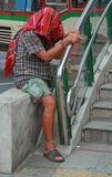 El hombre con la cabeza cubierta por la camisa pide al aire libre en Bangkok, Tailandia Foto de archivo