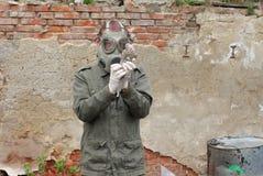 El hombre con la careta antigás y la ropa militar explora el pájaro muerto Imagen de archivo libre de regalías