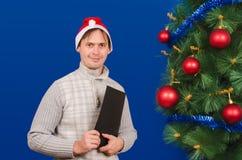 El hombre con la carpeta cuesta cerca de un árbol elegante del Año Nuevo Imágenes de archivo libres de regalías