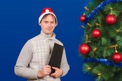El hombre con la carpeta cuesta cerca de un árbol elegante del Año Nuevo y Imagen de archivo