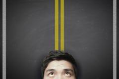 El hombre con la carretera amarilla alinea en la pizarra foto de archivo libre de regalías