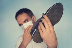 El hombre con la máscara está sosteniendo el zapato stinky sucio - concepto desagradable del olor Zapatillas de deporte hediondas fotos de archivo libres de regalías