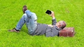 El hombre con la maleta que duerme en hierba y toma imágenes en el teléfono elegante almacen de video
