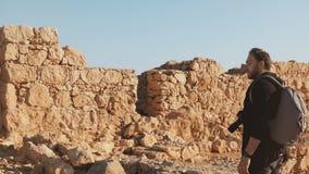 El hombre con la mochila camina en ruinas antiguas de las paredes Alzas turísticas masculinas caucásicas en rocas amarillas grand almacen de video