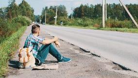 El hombre con la mochila se sienta en el camino en campo hitchhiking El esperar Smartphone almacen de video
