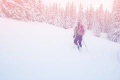 El hombre con la mochila va a snowshoeing encima de una colina Fotos de archivo