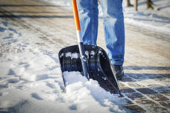 El hombre con la pala de la nieve limpia Fotos de archivo libres de regalías