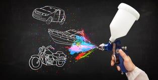 El hombre con la pintura de espray del aerógrafo con el coche, el barco y la motocicleta dibujan Fotografía de archivo libre de regalías
