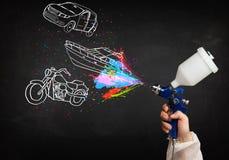 El hombre con la pintura de espray del aerógrafo con el coche, el barco y la motocicleta dibujan Imágenes de archivo libres de regalías