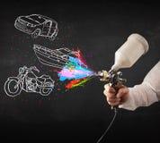 El hombre con la pintura de espray del aerógrafo con el coche, el barco y la motocicleta dibujan Imagen de archivo